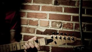 Guitar Against Brick